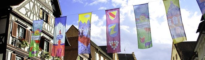 Sommer in der wolfacher Innenstadt - modern gestaltete Fahnen neben traditionellem Fachwerk.